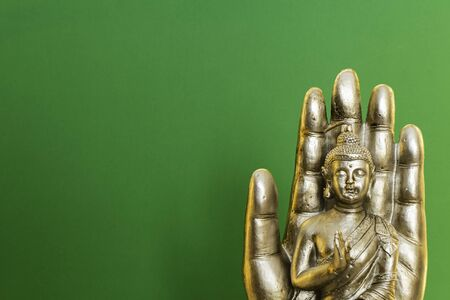 Buddha statue on green background.