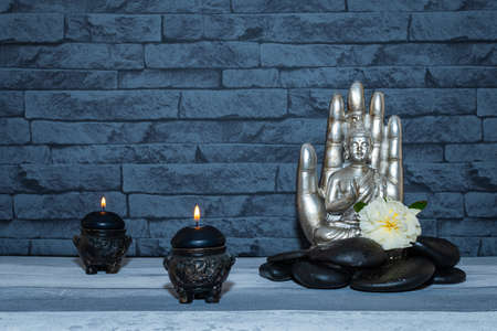 Buddha statue on the background of a stone wall with black pebbles and flowers.