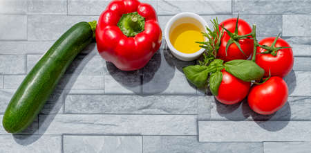 Creative presentation of summer seasonal vegetables with tomatoes, zucchini, red pepper, olive oil and fresh basil. On background to include text. 免版税图像