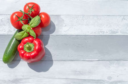 Creative presentation of summer seasonal vegetables with tomatoes, red pepper and fresh basil. On background to include text