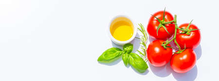 Creative presentation of seasonal summer vegetables with tomatoes, olive oil and fresh basil. On background to include text.