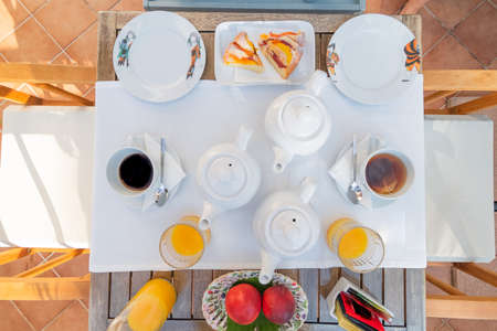 Breakfast for two served on a white tablecloth with coffee, tea, orange juice, fruit and cakes. 免版税图像