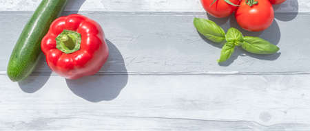 Creative presentation of seasonal summer vegetables with tomatoes, zucchini, red pepper and fresh basil. On background to include text.
