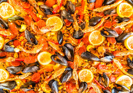 Paella dish with seafood, mussels, rice, lemon.