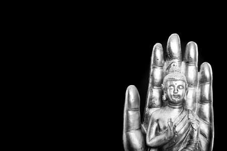 Buddha statue on black background.