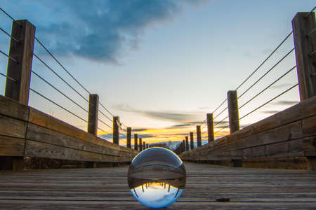 Glass ball on a pontoon in Camargue in France with sunset. 免版税图像