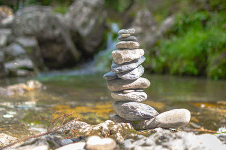 Stones stacked near a stream in the middle of nature, Zen atmosphere. 免版税图像