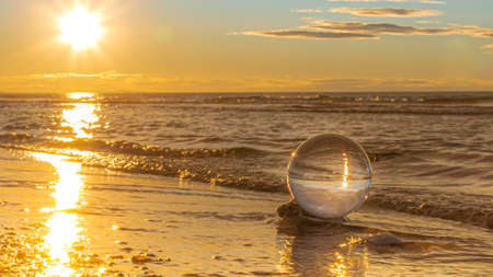 Crystal ball on pebbles of a beach at sunrise.