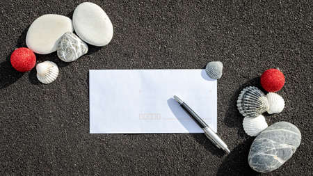 Sea sand grains background, black fine beach sand with envelope and pebbles and Christmas balls. Place for text on paper. Stock Photo