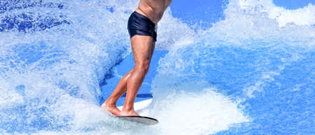 Adult man on a surfboard in a simulator to learn to surf.