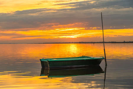 Fishing boat at the edge of a pond in the Camargue in the south of France at sunset.