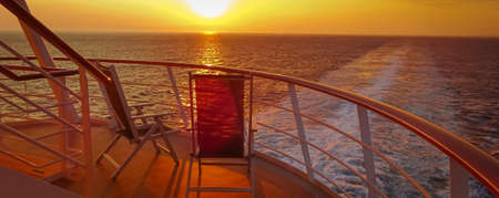 View from two lounge chairs on the deck of a cruise ship as the sun sets in the wake of the cruise ship. View from the stern of the ship.