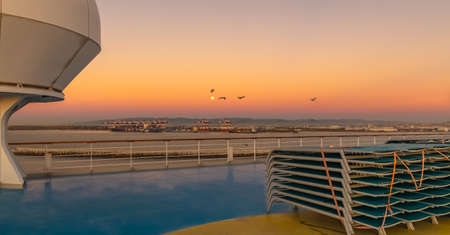View of lounge chairs on the deck of a cruise ship at sunset. View from the upper deck of the ship.