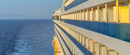 View of a cruise ship and balcony cabins while sailing on the sea.
