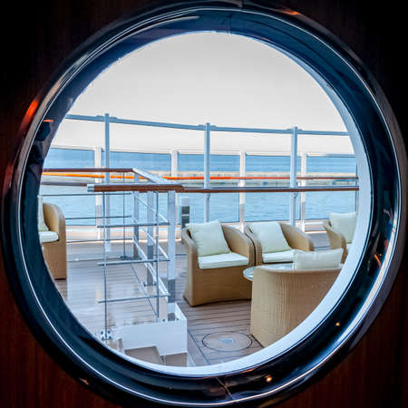 View of an outdoor lounge on the promenade deck of a cruise ship through a porthole.