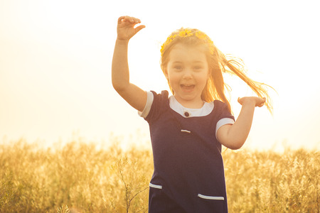 the beautiful little girl in a blue dress laughs, raising hands up photo