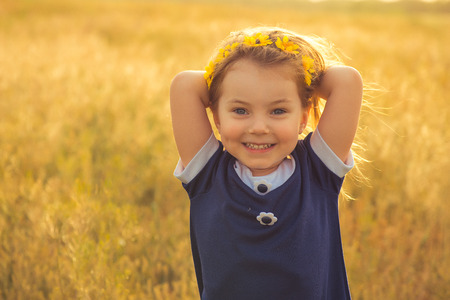 the beautiful little girl in a blue dress against a field laughs, holds hands behind the head photo