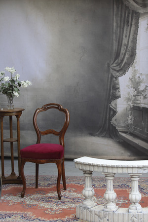 balustrade: typical old photo studio with chair table flowers and a marble balustrade Stock Photo