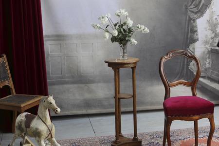 canicas: típico estudio fotográfico antiguo con silla, mesa, flores, caballito de madera y una balaustrada de mármol Foto de archivo