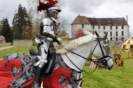 jousting: Harcourt, France - April 23, 2016: An unidentified man in a suit of armour is riding his horse to a mediaeval jousting tournament on Apr. 23, 2016 in Harcourt, France. It takes place in front of the castle Harcourt in Harcourt, France
