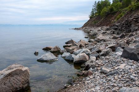 Orilla del lago Baikal con rocas y montañas en el horizonte
