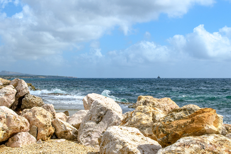 Seascape with huge rocks in the foreground, surf waves, ship silhouette on the horizon and blue sky with clouds.