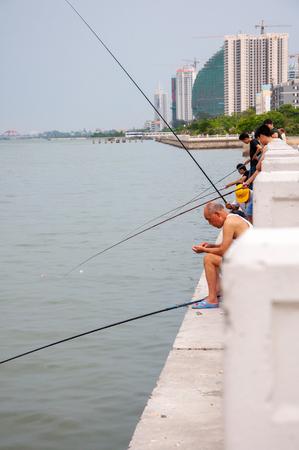 BEIHAI, CHINA - JUN, 2013: Fishermen fishing rods on the waterfront Beihai