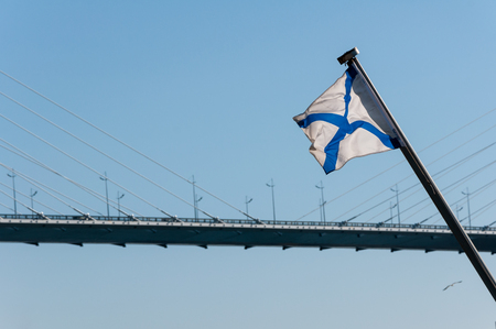 Russian naval flag on the background of cable-stayed bridge in Vladivostok through the Bosphorus East