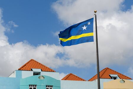 The blue-yellow Flag flutters in the blue cloudy sky above the tiled roofs and blue walls.