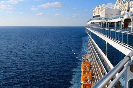 Blauwe Atlantische oceaan en witte wolken boven de horizon in blauwe lucht met cruiseschipperspectief en oranje reddingsboten. Stockfoto