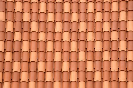 Fragment of a tiled roof. Clay tiles. Background. Pattern. Terracotta. Gray. Ocher.