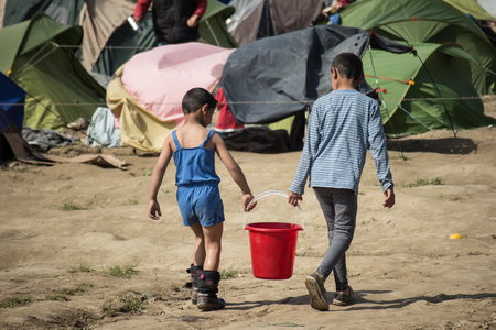 Idomeni, Paeonia, Kilkis regional unit of Central Macedonia / Greece - March 22 2016: two kids carrying a bucket of water in the tents where they live in the refugee camp of Idomeni.