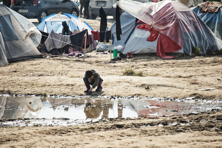 Idomeni, Paeonia, Kilkis regional unit of Central Macedonia / Greece - March 22 2016: a kid looking in the mirror of a pond in the refugee camp. Editorial