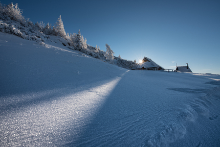 The sun setting behind a typical herdmens house in the alpine plateau of Velika Planina, Slovenia. Stockfoto