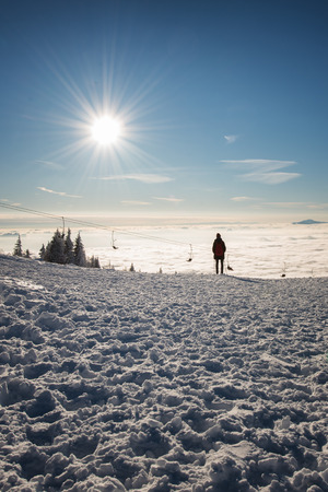 The silhouette of a hiker looking at the sea of cloud from Velika Planina, alpine plateau in Slovenia.