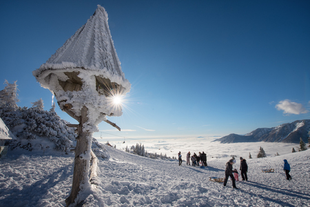 People having fun on a sunny winter day in Velika Planina, Slovenia.