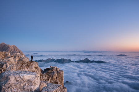 Hiker watching sunrise above the clouds in the Italian Julian Alps.