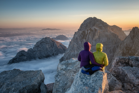 A couple of hikers hugging and enjoying an alpine sunrise.
