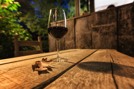 A glass of red wine and a brown autumn leaf on a wooden table in Friuli, Italy.