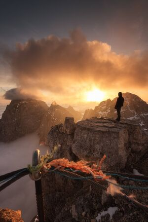 Hiker enjoying sunris from the top of a mountain in the Alps