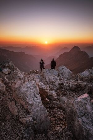 Hikers enjoying sunset from the top of a mountain in the Alps