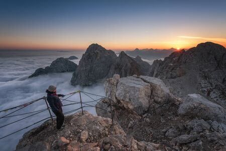 Hiker enjoying sunrise from the top of a mountain in the Alps Stock fotó