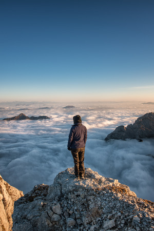 A hiker above the clouds, looking at the horizon. Stockfoto