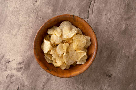 Potato chips on a wooden bowl over wood background