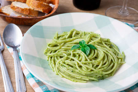 Spaghetti with pesto on a white and green plate with bread and a glass of wine