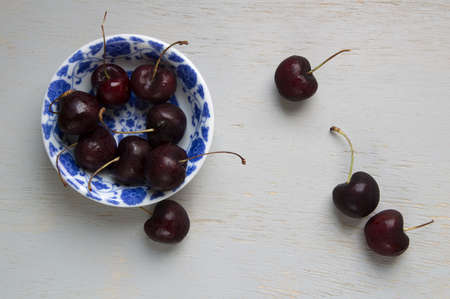 Black cherries on a white and blue vintage bowl over woodwn table
