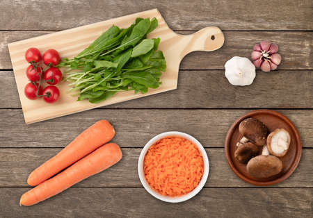 Vegetables and salad ingredients over wooden table.