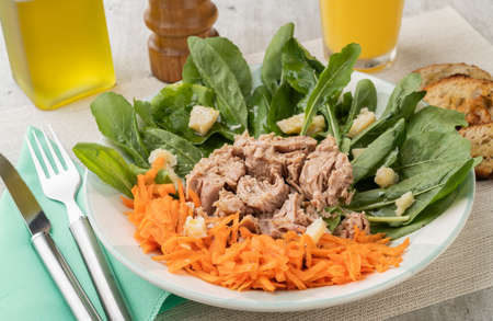Rucula, tuna, parmesan and carrot salad with olive oil and orange juice.