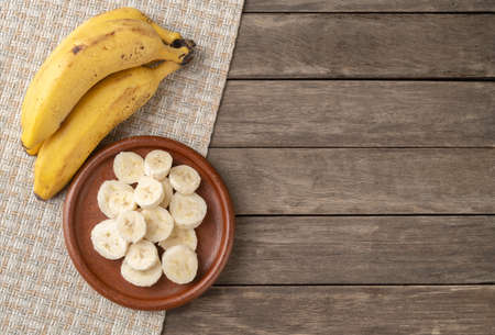 Bananas and slices over wooden table with copy space.