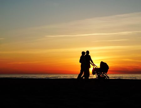 Young pair with a childrens carriage on a beach